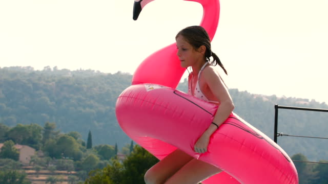 Young girl with an inflatable pink flamingo jumping into the pool in slow motion