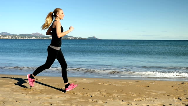 Young girl with earphones and smart watch running on beach
