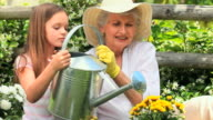 Young girl with her grandmother watering a plant / Cape Town, Western Cape, South Africa