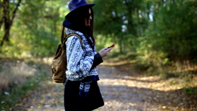 Young girl with phone hiking in the forest