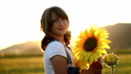 Young girl with sunflowers at sunset