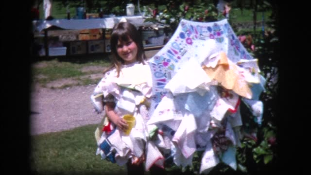 1968 young girl with umbrella and clothing covered with colorful handkerchiefs
