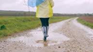 SLO-MO-junge Mädchen mit Regenschirm überspringen durch eine Pfütze