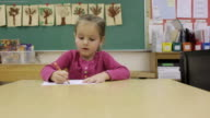 MS Young girl working on writing inside classroom at school / Minneapolis, Minnesota, United States