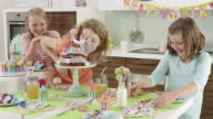 3 young girls celebrating birthday and eating birthday cake