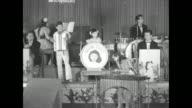 Young girls from Nakagawa Troupers on stage with adult show band and conductor youngest girl sits at drum set with Nakagawa logo preteen at piano and...