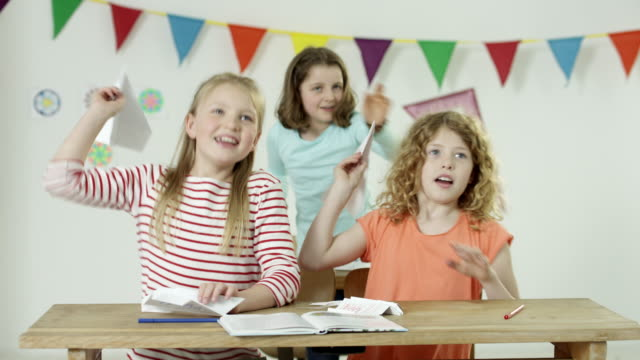 young girls in classroom - having fun throwing paper planes
