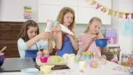 3 young girls preparing a birthday party in the kitchen