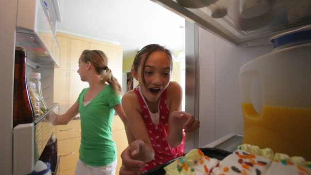 Young girls steal birthday cake from refrigerator