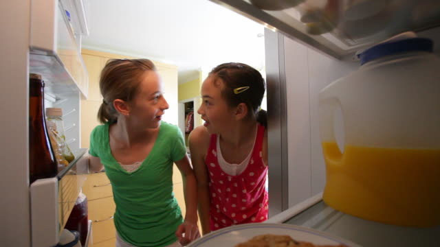 Young girls steal cookies from refrigerator