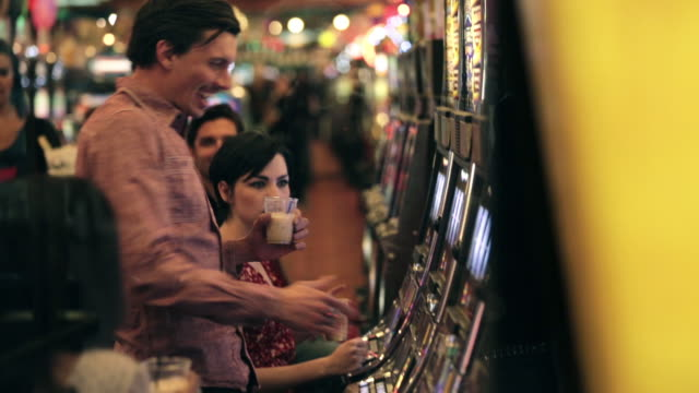 Young guy wins big at casino slot machine, kisses young woman and celebrates with friends