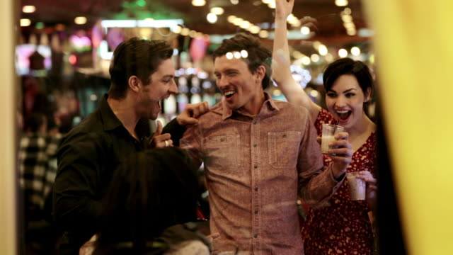 Young guy wins big at casino slot-machine, celebrates with friends