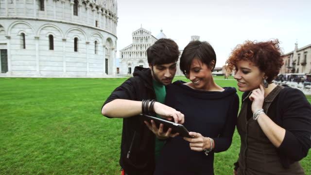 Junge Männer, die mit einem digitalen Führer der Piazza dei Miracoli