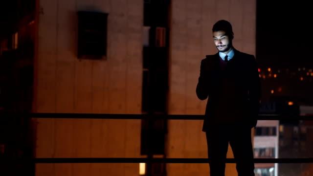 Jonge knappe man met behulp van de telefoon op dak