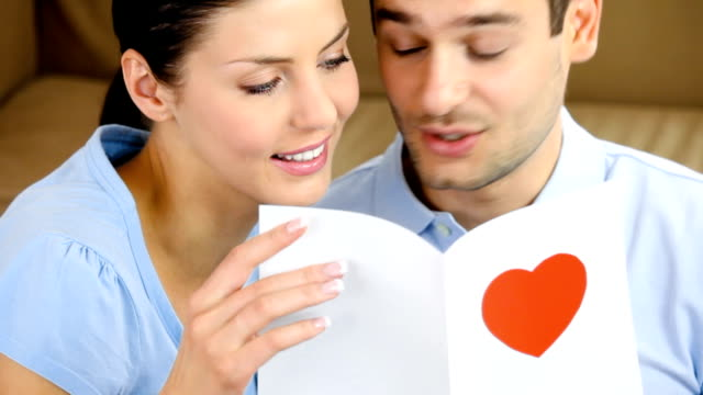 Young happy couple reading greeting card together at home