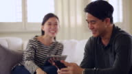 CU Young happy couple using digital tablet and smartphone at home