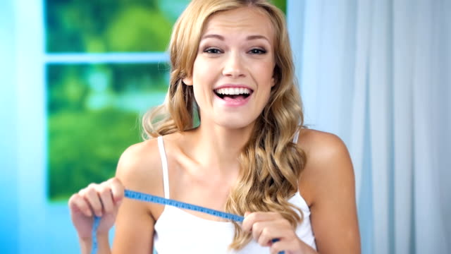 Young happy smiling woman measure tape, at home