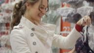 Junge glückliche Frau Wählen Sie Kleidung in Dessous kaufen