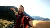 Young hiker takes selfie from mountain top