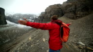 Young hiker walks along mountain ridge crest