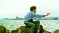 Young hipster man filming the San Francisco Skiline from the Treasure Island in front of San Francisco view.