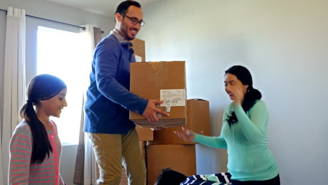 Young Hispanic family packing boxes and moving from suburban home