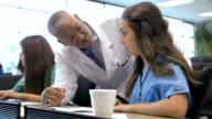 Young Hispanic nursing student being tutored by senior professor of medicine