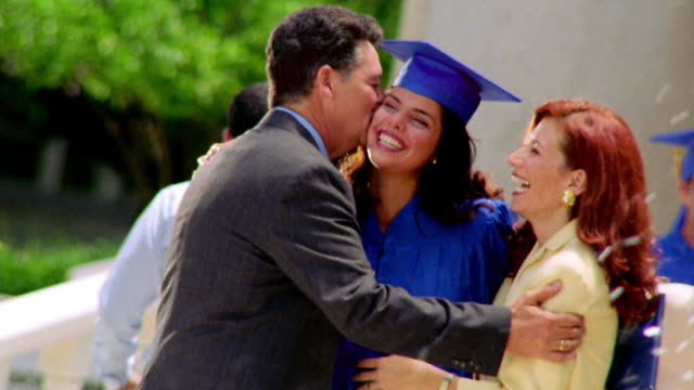 CANTED MS young Hispanic woman in cap + gown holding diploma + hugging parents outdoors / Florida