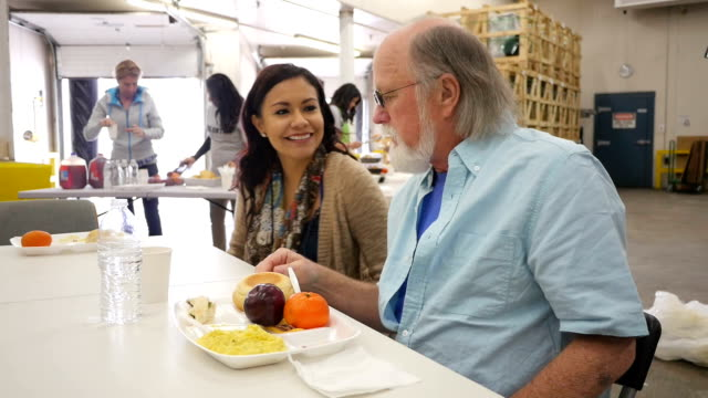 Young Hispanic woman volunteering to assist seniors in community soup kitchen