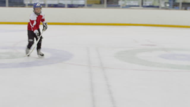 MS Young hockey player skating up to camera on ice rink giving victory sign