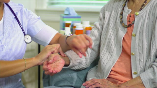 CU TU Young home health care worker taking senior woman's pulse, Austin, Texas, USA
