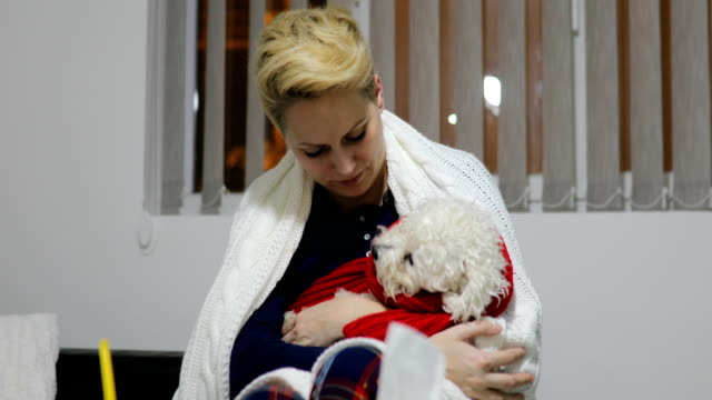 Young ill woman with tissue and pet .