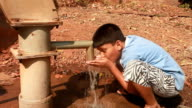 Young Indian boy drinking water from hand pump