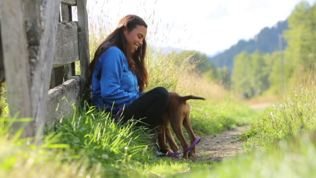 Jonge inheemse Canadese vrouw speelt met haar hond