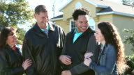 Young interracial couple with her parents outside house