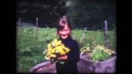 1964 young lady holds yellow flowers in Alpine setting