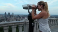 MS TU Young lady looking through binoculars at montreal skyline from top of Mount Royal / Montreal, Quebec, Canada