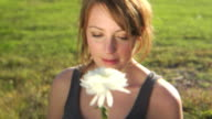 HD-KRAN: Junge Frau riecht an einer Blume