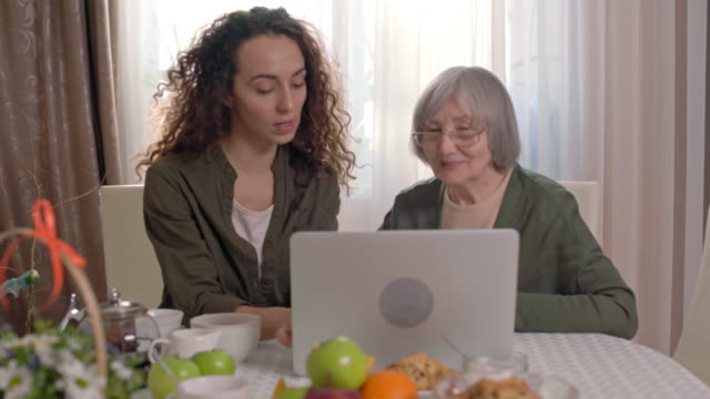 Young lady teaching old woman how to use laptop