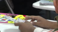 MS Young Latino boy hands holding math subtraction Flashcards at table discarding them to left young unidentifiable boy picking up cards FG Hispanic...