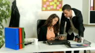 Young male and female office workers colleagues looking at tablet and brainstorming a project