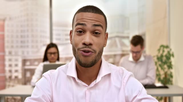 Jonge mannelijke architect maken van een video-oproep van het bureau