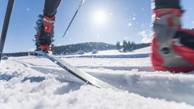 Young male athlete cross country skiing on ski track