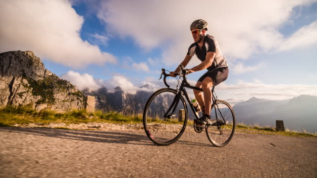 Young male athlete cycling on a mountain pass at sunset