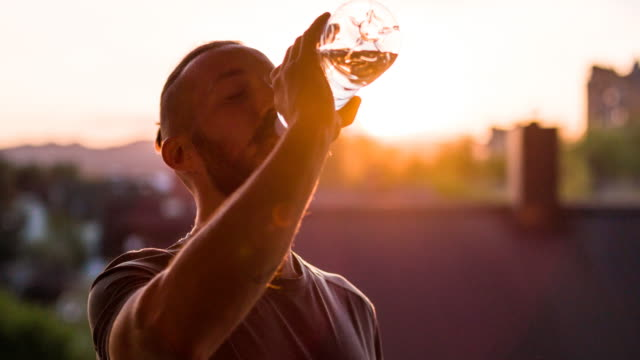 Young male athlete drinking water after finishing a run