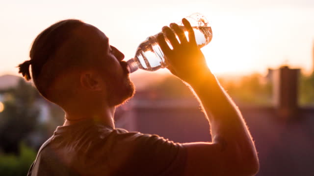 Young male athlete drinking water at sunset after working out