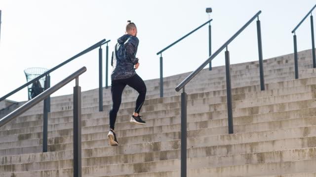 Jonge mannelijke atleet lopen de trap