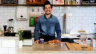 Young Male Barista Standing With Coffee And Food