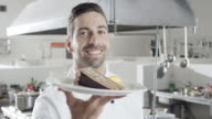 Young male chef showing cake