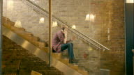 A young male creative professional uses smartphone on the stairs of modern office.